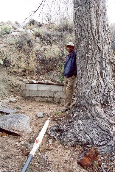 Shetty posing next to pipe drawing water from spring well near Arroyo San Salvador, Sierra Juarez, Baja California, March 16, 2002.